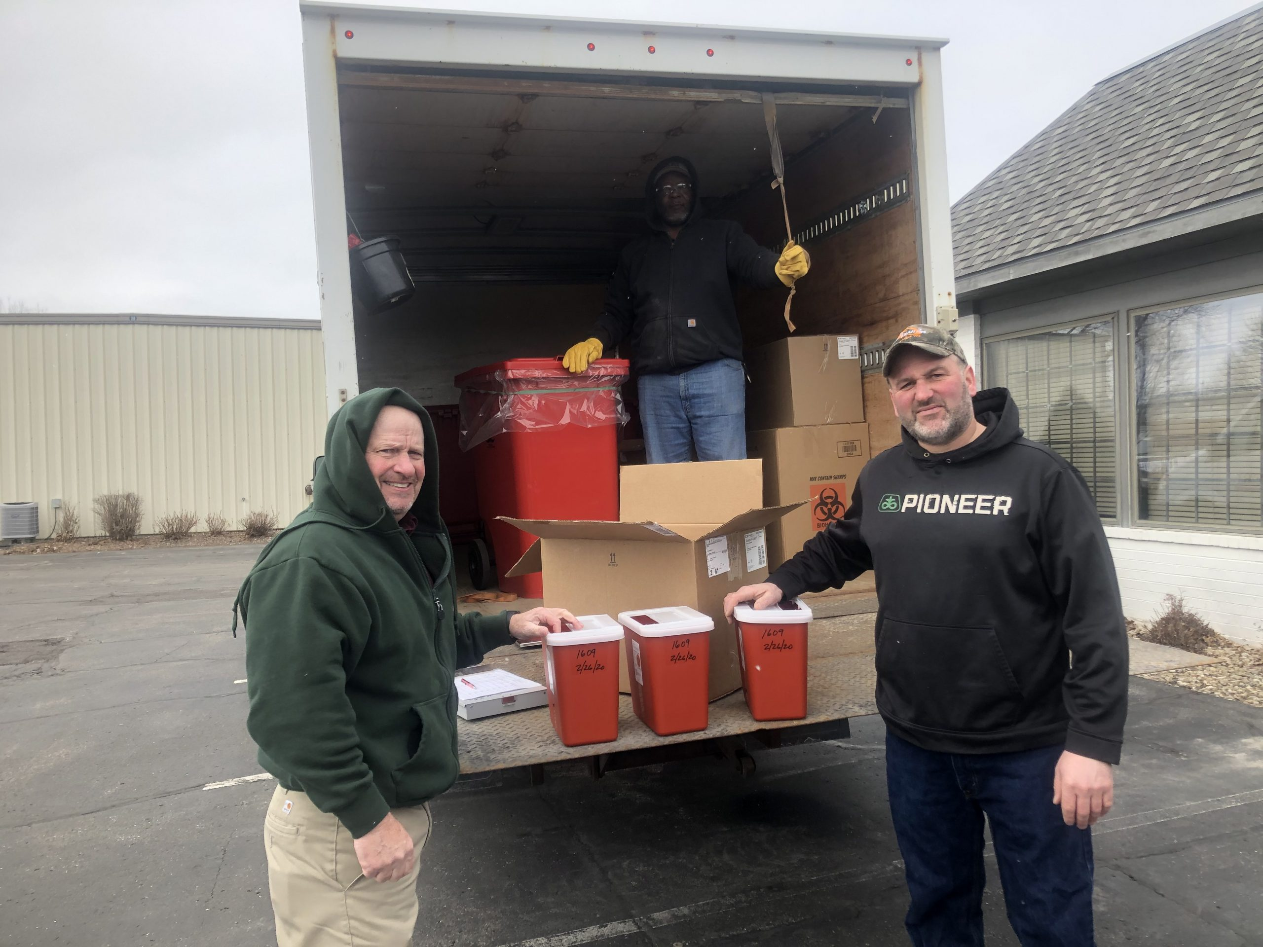 Top: MERI's Tyrone McGee is on hand as Grande's Randy Hardyman (left) hands producer Hardy Ripp a biohazard container as part of the sharps collection event held recently in Waunakee