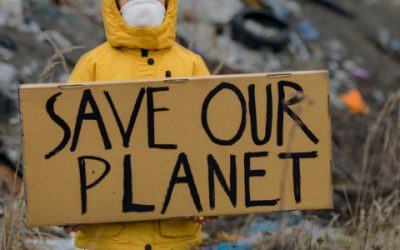 Save Our Planet Sign held by child in front of landfill